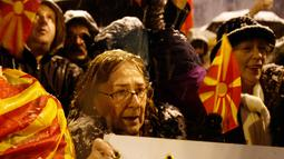 Seorang wanita berpartisipasi dalam protes wacana pengubahan nama Macedonia di gedung Parlemen, Skopje, Selasa (27/2). Pengunjuk rasa mendesak pemerintah mengakhiri dialog dengan Yunani untuk menyelesaikan sengketa selama 25 tahun (AP/Boris Grdanoski)