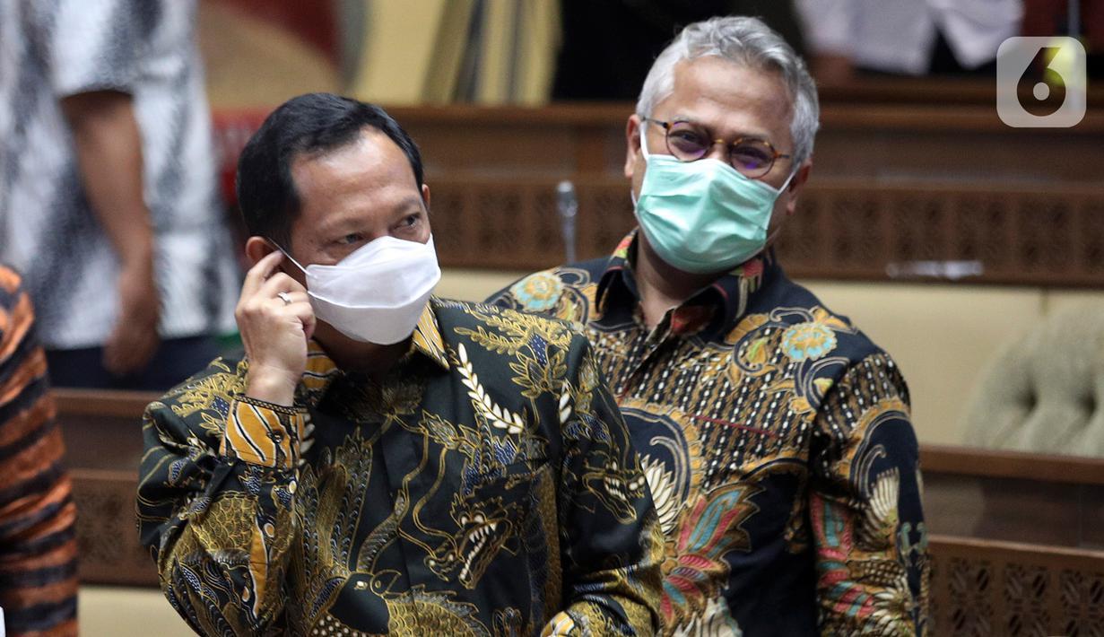 Mendagri Tito Karnavian (kiri) bersama Ketua KPU Arief Budiman sebelum mengikuti rapat kerja dengan Komisi II DPR di Kompleks Parlemen, Senayan, Jakarta, Kamis (26/11/2020). Rapat itu membahasan data kependudukan dan data pemilih Pilkada Serentak 2020. (Liputan6.com/Johan Tallo)