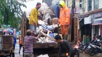 Petugas mengangkut sampah akibat banjir di Tangerang. (Liputan6.com/Pramita Tristiawati)