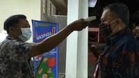Seorang peserta rapat pembahasan PSBB di Malang Raya diukur suhu badannya untuk mencegah potensi penyebaran Corona Covid-19 (Liputan6.com/Zainul Arifin)