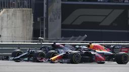 Namun pada lap pertama, kedua pembalap terlibat insiden. Max Verstappen dan Lewis Hamilton bersenggolan di sektor Copse. Imbasnya mobil Verstappen melintir keluar dan menabrak bantalan ban pembatas sirkuit. (Foto: AP/Jon Super)