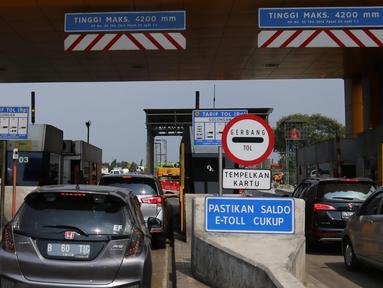 Pengendara mengantre melakukan transaksi di pintu masuk tol ruas Tangerang, Banten, Rabu (17/7/2019). PT Jasa Marga (Persero) Tbk resmi menggandeng LinkAja untuk mendukung sistem penerapan transaksi nir sentuh atau Single Lane Free Flow (SLFF) di jalan tol. (Liputan6.com/Angga Yuniar)
