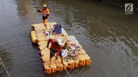Petugas UPK Badan Air Pemprov DKI Jakarta membersihkan ceceran sampah di sepanjang Anak Sungai Ciliwung yang membelah kawasan Jalan Gajah Mada dan Hayam Wuruk, Selasa (9/7/2019). Pembersihan ini untuk menghindari penumpukan sampah dan memperlancar aliran air. (Liputan6.com/Helmi Fithriansyah)