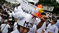 Demonstran memakai aksesoris berbentuk ayam saat unjuk rasa depan Istana Merdeka, Jakarta, (1/3). Dalam aksinya mereka membawa 1 truk ternak ayam untuk menyampaikan rasa kecewa terhadap turunnya Harga Pokok Produksi (HPP). (Liputan6.com/Faizal Fanani)