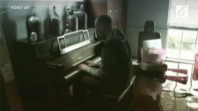 Korban badai harvey bermain piano di rumahnya yang terendam. Pria tersebut adalah seoarang pastor bernama aric harding.
