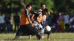 Penduduk desa bermain sepak bola dengan mengenakan sarung saat merayakan HUT ke-74 RI di Blang Pidie provinsi Aceh (17/8/2019). Indonesia merayakan kemerdekaan yang ke-74 dari pemerintahan kolonial Belanda. (AFP Photo/Chaideer Mahyuddin)