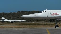 Dua pesawat pengebom jarak jauh jenis TU-160 ketika mendarat di Bandara Internasional Simón Bolívar, dekat Caracas, Senin (10/12). Rusia mengerahkan empat pesawat militer ke Venezuela untuk mengikuti latihan gabungan kedua negara. (Federico PARRA / AFP)