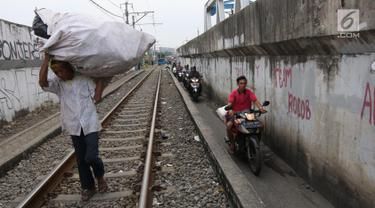 Sejumlah pengendara melintas di samping rel kereta yang berada di kawasan Banjir Kanal Barat, Jakarta, Selasa (20/3). Aksi nekat itu dilakukan dengan alasan demi mempersingkat waktu. (Liputan6.com/Arya Manggala)