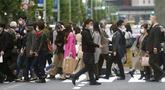 Orang-orang yang mengenakan masker untuk membantu mengekang penyebaran virus corona COVID-19 berjalan melintasi penyeberangan pejalan kaki di Tokyo, Jepang, Rabu (28/10/2020). Tokyo mengonfirmasi lebih dari 170 kasus virus corona COVID-19 baru pada 28 Oktober 2020. (AP Photo/Eugene Hoshiko)