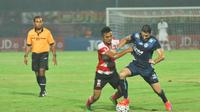 Pemain Madura United, Asep Berlian berebut bola dengan pemain asing Arema Cronus, Srdan Lopicic dalam pertandingan yang berakhir imbang 0-0 di Stadion Gelora Bangkalan, Jawa Timur, Jumat (6/5/2016). (Bola.com/Iwan Setiawan)