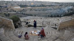 Warga Palestina berkumpul untuk berbuka puasa selama bulan suci Ramadan dengan latar belakang Kota Tua Yerusalem dan kompleks Masjid al-Aqsa yang ditutup selama krisis pandemi coronavirus di Bukit Zaitun (19/5/2020). (AFP/Ahmad Gharabli)
