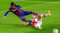 Pemain Barcelona, Junior Firpo, terjatuh saat berebut bola dengan pemain Alaves, Edgar Mendez, pada laga Liga Spanyol di Stadion Camp Nou, Sabtu (14/2/2021). Barcelona menang dengan skor 5-1. (AP Photo/Joan Monfort)