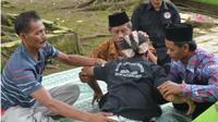 Fajar (mengenakan blangkon) saat mengalami kesurupan di lokasi makam tua Siti Hinggil. (KRJogja.com/Gunarwan)