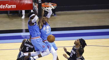 Pebasket Houston Rockets, Christian Wood, memasukan bola saat melawan Sacramento Kings pada laga NBA, Jumat (1/1/2021). Houston Rockets menang dengan skor 122-119. (AP/Richard Carson)