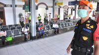 Petugas gabungan dari Polrestabes Semarang menyemprot larutan disinfektan kepada penumpang yang turun di Stasiun KA Tawang, Sabtu (28/3/2020). Selain sterilisasi, petugas juga melakukan pencatatan penumpang yang turun untuk data pengawasan guna menekan penularan Corona COVID-19. (Liputan6.com/Gholib