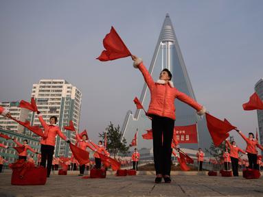 Kelompok Serikat Wanita Sosialis mengibarkan bendera saat melakukan propaganda di depan Hotel Ryugyong, Pyongyang, Korea Utara, Sabtu (9/3). Mereka mengibar-ngibarkan bendera sambil menyanyikan lagu-lagu patriotik selama jam sibuk. (Ed Jones/AFP)