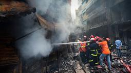Petugas pemadam kebakaran berusaha memadamkan api setalah api melahap gedung apartemen yang juga digunakan sebagai gudang bahan kimia di Dhaka (21/2). Setidaknya 69 orang tewas dalam kebakaran besar tersebut. (AFP Photo/Munir Uz Zaman)