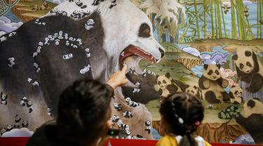 Pengunjung mengamati lukisan thangka bertema panda di Perpustakaan Provinsi Sichuan, Chengdu, Provinsi Sichuan, China, 11 Oktober 2020. Lebih dari 40 pelukis thangka menghabiskan waktu setahun untuk menyelesaikan lukisan yang memiliki panjang 172 meter dan tinggi 2,6 meter tersebut. (Xinhua/Wang Xi)