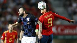 Striker Spanyol, Rodrigo Moreno, duel udara dengan gelandang Kroasia, Marcelo Brozovic, pada laga UEFA Nations League di Stadion Manuel Martinez Valero, Selasa (11/9/2018). Spanyol menang 6-0 atas Kroasia. (AP/Alberto Saiz)