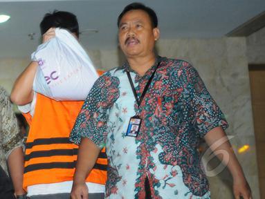 Direktur PT Mitra Maju Sukses, Andrew Hidayat menutup wajahnya usai menjalani pemeriksaan di Gedung KPK, Jakarta, Sabtu (11/4/2015), dini hari. Andrew ditangkap KPK bersama barang bukti uang senilai  US$ 90.000. (Liputan6.com/Herman Zakharia)
