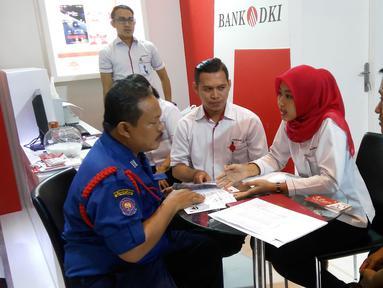 Karyawan Bank DKI menjelaskan aplikasi JakOne Mobile kepada pengunjung Pekan Raya Jakarta di Jakarta (23/5). Bank DKI turut berpartisipasi dalam PRJ yang digelar mulai tanggal 23 Mei hingga 1 Juni. (Liputan6.com/Pool/Budi)
