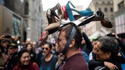 Seorang pria memakai topi yang terbuat dari sepatu wanita dalam Parade Paskah tahunan dan Festival Bonnet di sepanjang Fifth Avenue, New York, AS, Minggu (21/4). Parade Bonnet Easter merupakan parade pada perayaan Paskah di Kota New York yang sudah ada sejak tahun 1870. (Johannes EISELE / AFP)