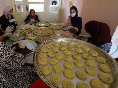 Para perempuan Palestina dengan masker dan sarung tangan menyiapkan biskuit tradisional menjelang Idul Fitri di sebuah rumah di kota tua Hebron, Tepi Barat yang diduduki, Selasa (19/5/2020). Biskuit-biskuit itu akan dijual secara online guna menjaga jarak selama pandemi Covid-19. (HAZEM BADER/AFP)
