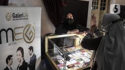 Calon pembeli mencoba cincin emas di Pegadaian, Jakarta, Selasa (18/5/2021). Berdasarkan informasi dari Unit Bisnis Pengolahan dan Pemurnian Logam Mulia Antam, harga dasar emas 24 karat ukuran 1 gram dijual senilai Rp 937.000, naik Rp 4.000 per gram dari harga sebelumnya. (Liputan6.com/Johan Tallo)