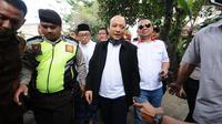 Penyidik KPK, Novel Baswedan (jas hitam) berjalan menuju kediaman di kawasan Kelapa Gading, Jakarta, Kamis (22/2). Novel kembali dalam proses pemulihan sambil menunggu jadwal operasi tahap kedua. (Liputan6.com/Helmi Fithriansyah)
