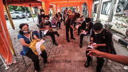 Peserta mengisi data administrasi saat akan menerima vaksin di Sentra Vaksinasi Covid-19, GOR Kemayoran, Jakarta, Kamis (3/6/2021). Sentra Vaksinasi Covid-19 ini menyasar 30 ribu karyawan ritel dan UMKM dengan target 1.000 orang per hari selama satu bulan ke depan. (merdeka.com/Iqbal S Nugroho)