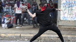 Seorang demonstran anti-pemerintah melemparkan batu ke arah polisi di Santiago, Chile (4/10/2019). Pengunjuk rasa menuntut diakhirinya ketidaksetaraan ekonomi bahkan ketika pemerintah mengumumkan bahwa demonstrasi selama berminggu-minggu merugikan pertumbuhan ekonomi negara. (AP Photo/Esteban Felix)
