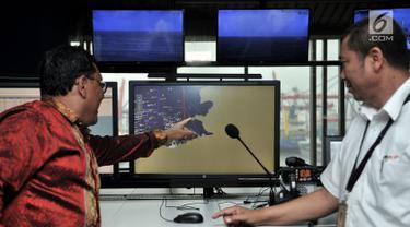 Direktur Operasional dan Sistem Informasi PT Pelindo II/IPC Prasetyadi (kiri) menjelaskan sistem kerja Vessel Traffic System (VTS) di Kantor IPC, Tanjung Priok, Jakarta, Senin (21/1). IPC menerapkan sistem VTS dan VMS. (Merdeka.com/Iqbal Nugroho)