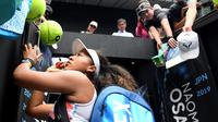 Petenis Jepang Naomi Osaka menandatangani benda yang disodorkan penonton usai mengalahkan petenis Republik Ceko Marie Bouzkova pada Australia Terbuka di Melbourne, Australia, Senin (20/1/2020). Penonton menyodorkan topi, bendera, hingga bola untuk ditandatangani Naomi. (AP Photo/Andy Brownbill)