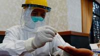 Petugas mengambil sampel darah warga Pekanbaru dalam rapid tes Covid-19. (Liputan6.com/M Syukur)