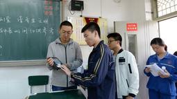 Pengawas mengidentifikasi peserta ujian masuk perguruan tinggi di Handan, Provinsi Hebei, China, (6/6). Melalui simulasi ini dapat diketahui bahwa peserta ujian harus melewati beberapa pemeriksaan sebelum memasuki ruangan. (AFP/STR)