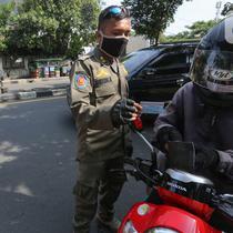 Petugas memeriksa identitas pengendara bermotor pada hari pertama PSBB di jalur check point Jalan Ir. H Juanda, Ciputat, Tangerang Selatan, Sabtu (18/4/2020). PSBB resmi diberlakukan di Kabupaten Tangerang, Kota Tangerang dan Tangerang Selatan hingga 1 Mei 2020. (Liputan6.com/Fery Pradolo)
