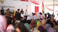 Presiden Jokowi menyerahkan secara simbolis buku rekening PKH dan KIP (Liputan6.com / Nefri Inge)