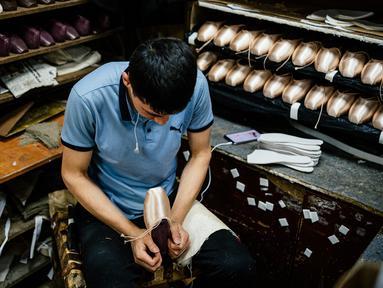 Pekerja menyelesaikan pembuatan sepatu pointe di bengkel perusahaan Grishko, Moskow, Rusia, 25 Februari 2020. Grishko yang lahir dalam kekacauan runtuhnya Uni Soviet sekarang menjadi salah satu pembuat sepatu balet top dunia. (Dimitar DILKOFF/AFP)
