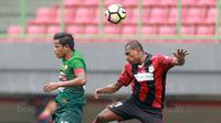 Duel udara pemain Persipura Jayapura, Yustinus Pae (kanan) dan pemain PS TNI, Manahati Lestusen  pada lanjutan Liga 1 2017 di Stadion Patriot, Bekasi (4/11/2017). PS TNI menang 2-1. (Bola.com/Nick Hanoatubun)
