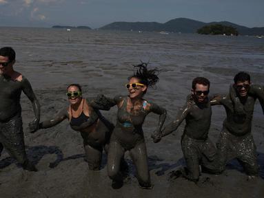 "Peserta bermain lumpur selama pesta karnaval ""Bloco da Lama"" atau ""Lumpur Lumpur"" di Paraty, Brasil, (10/2). Ratusan orang berendam dan saling menyerang menggunakan lumpur sambil menari samba di pesta pantai Karnaval tersebut. (AP Photo / Leo Correa)"