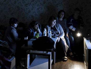 Warga menonton TV Negara saat berkumpul dalam tempat penampungan untuk melindungi diri dari serangan bom di Stepanakert, Republik Nagorno-Karabakh, Azerbaijan, 28 September 2020. Pasukan Armenia dan Azerbaijan bertempur atas wilayah separatis Nagorno-Karabakh. (Armenian Foreign Ministry via AP)