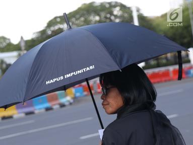 Aktivis melaksanakan aksi kamisan perdana di tahun 2019 di depan Istana Negara, Jakarta, Kamis (3/1). Mereka meminta pemerintah menuntaskan penyelesaian kasus pelanggaran HAM masa lalu. (Liputan6.com/Helmi Fithriansyah)