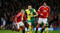 Kapten Norwich City, Russell Martin (tengah), coba melewati hadangan dua gelandang Manchester United, Memphis Depay dan Marouane Fellaini di Old Trafford, Sabtu (19/12/2015) malam WIB. (Reuters/Andrew Yates)