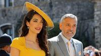 Amal Clooney (kiri) dan George Clooney saat menghadiri upacara pernikahan Pangeran Harry dan Meghan Markle di St. George's Chapel, Windsor Castle, Windsor, dekat London, Inggris, Sabtu (19/5). (Gareth Fuller/pool photo via AP)
