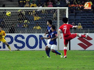 Tendangan keras pemain Singapura, Shi Jiayi (paling kanan) ke gawang Malaysia yang dikawal Mohamad Farizal (paling kiri) dalam Laga Piala AFF Suzuki 2012 di Stadion Bukit Jalil, Kuala Lumpur, Malaysia, minggu 25 November 2012. pertandingan berakhir 0-3 un