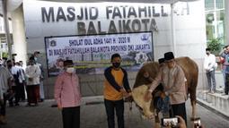 Gubernur DKI Jakarta Anies Baswedan (kanan) menyerahkan sapi kurban di Balai Kota, Jakarta, Jumat (31/7/2020). Pada Hari Raya Idul Adha tahun ini, Anies menyumbangkan sapi kurban jenis limosin seberat 1,3 ton. (Liputan6.com/Immanuel Antonius)