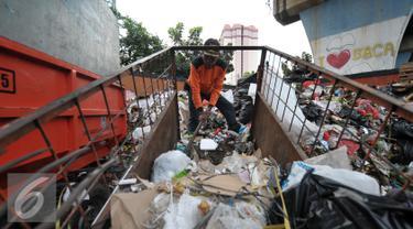 Petugas kebersihan mengumpulkan sampah di lokasi tempat pembuangan sampah sementara (TPSS), Pasar Baru, Jakarta, Jumat (25/11). Pengelolaan sampah menjadi pekerjaan rumah bagi calon gubernur DKI Jakarta yang terpilih nanti. (Liputan6.com/Yoppy Renato)