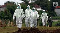 Petugas usai membawa jenazah yang dimakamkan dengan protokol COVID-19 di area khusus TPU Srengseng Sawah, Jakarta, Selasa (19/1/2021). Hingga Selasa (19/1) siang, TPU Srengseng Sawah telah memakamkan 388 jenazah dengan protokol COVID-19 atau setengah kapasitas. (Liputan6.com/Helmi Fithriansyah)