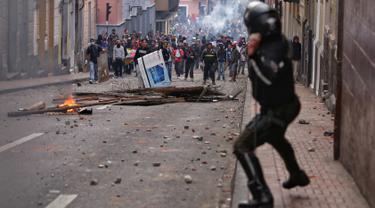 Polisi anti huru hara saat menghadapi demonstran selama bentrokan di Quito (7/10/2019). Para demonstran memprotes terhadap keputusan Presiden Ekuador Lenin Moreno yang mencabut subsidi bahan bakar. (AFP Photo/Cristina Vega)