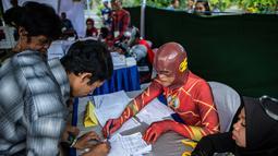 Petugas Kelompok Penyelenggara Pemungutan Suara (KPPS) berkostum superhero The Flash mendata warga yang akan mencoblos dalam Pemilu 2019 di sebuah TPS di Surabaya, Jawa Timur, Rabu (17/4). Ada sembilan petugas KPPS yang mengenakan kostum superhero di TPS ini. (Juni Kriswanto/AFP)